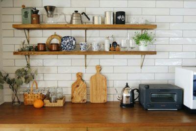 キッチン背面はタイルと足場板でインテリアを楽しむ。